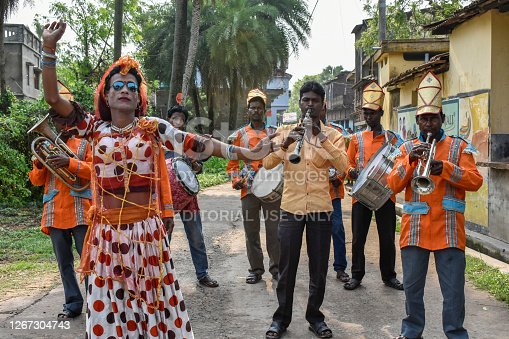 Barddhaman, West Bengal, India - April 17, 2019; A musical marching band performing their music on the roads of a village in West Bengal of India and a man in the guise of a woman is performing a dance.