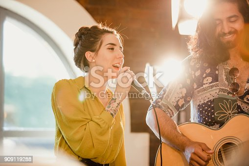 Musical performers at an event. There is a female singer and a male guitarist.