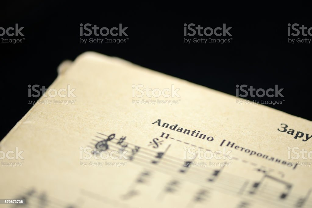Musical tempo 'Andantino' in an old music notebook close up stock photo