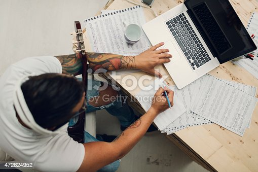 Top view of an man with acoustic guitar composing music for iStock and Getty stock library. Using laptop and writing lyrics or music notes.