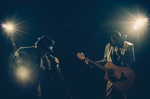 Musician Duo band hand holding the microphone and singing a song and playing the guitar on black background with spot light and lens flare, musical concept