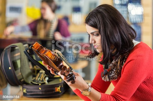Mid adult woman is examining a beautiful violin that she is purchasing from a small local business that sells and repairs musical instruments. Musician is supporting small business by purchasing custom instrument. She is examining strings and standing next to counter with open violin case.