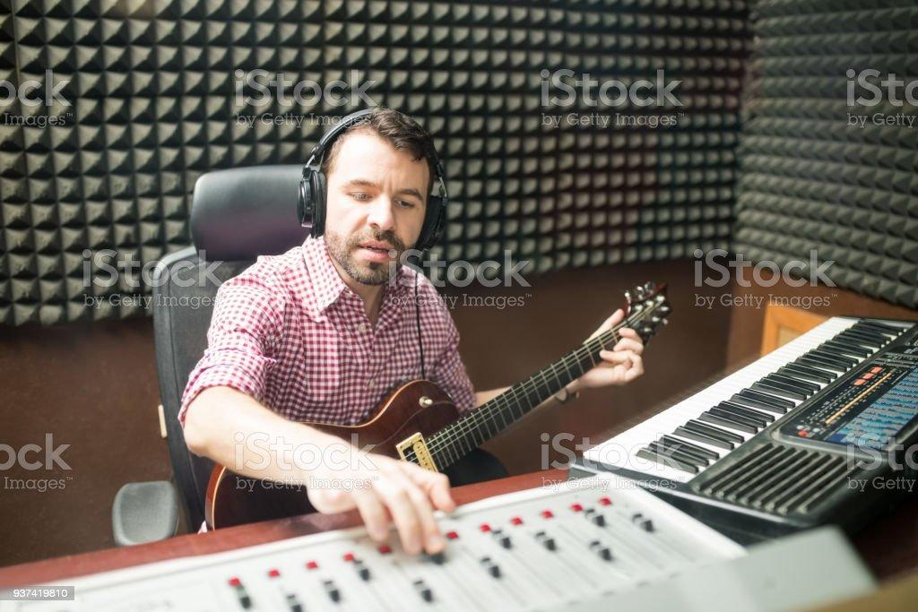 Musician fine tuning the sounds in recording studio stock photo