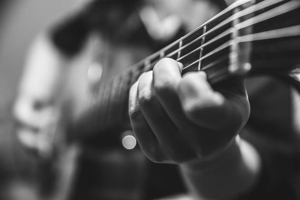 musician guitar player plays the guitar closeup vintage tone with noise grain effect musician guitar player plays the guitar closeup vintage tone with noise grain effect guitarist stock pictures, royalty-free photos & images