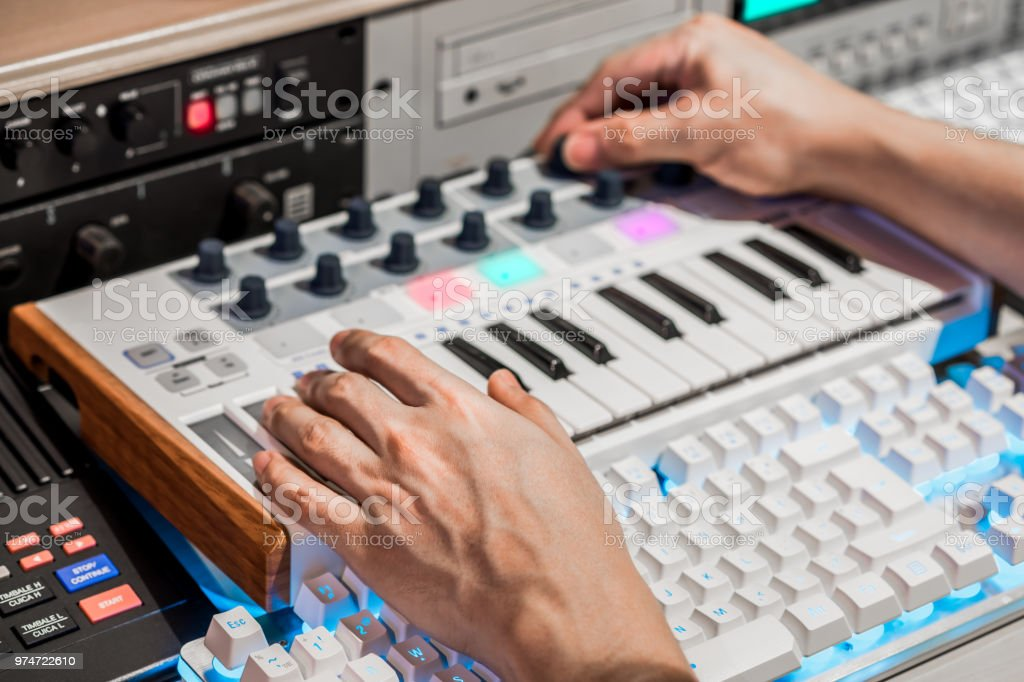 Photo de stock de musicien mains ajuster le bouton clavier midi pour