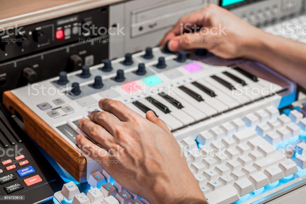 musician hands adjust midi keyboard knob for recording in digital sound editing studio stock photo