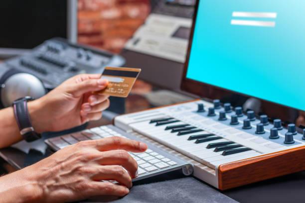 musiker hände halten kreditkarte für online-shopping in musikstudio - klavier verkaufen stock-fotos und bilder