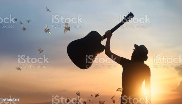 Musician holding guitar in hand with free bird of silhouette on picture id881359064?b=1&k=6&m=881359064&s=612x612&h=31szc4mjsa9g6yozvpytyvu juho3naz50xmbbv6g84=