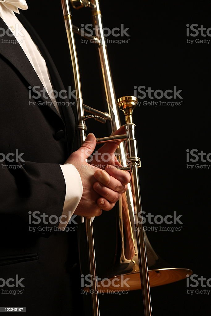 Musician holds a trombone against  black background stock photo