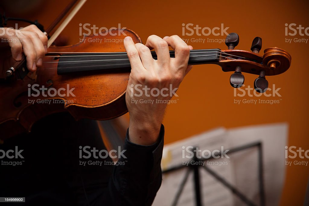 Musician in black playing violin over an orange backdrop royalty-free stock photo