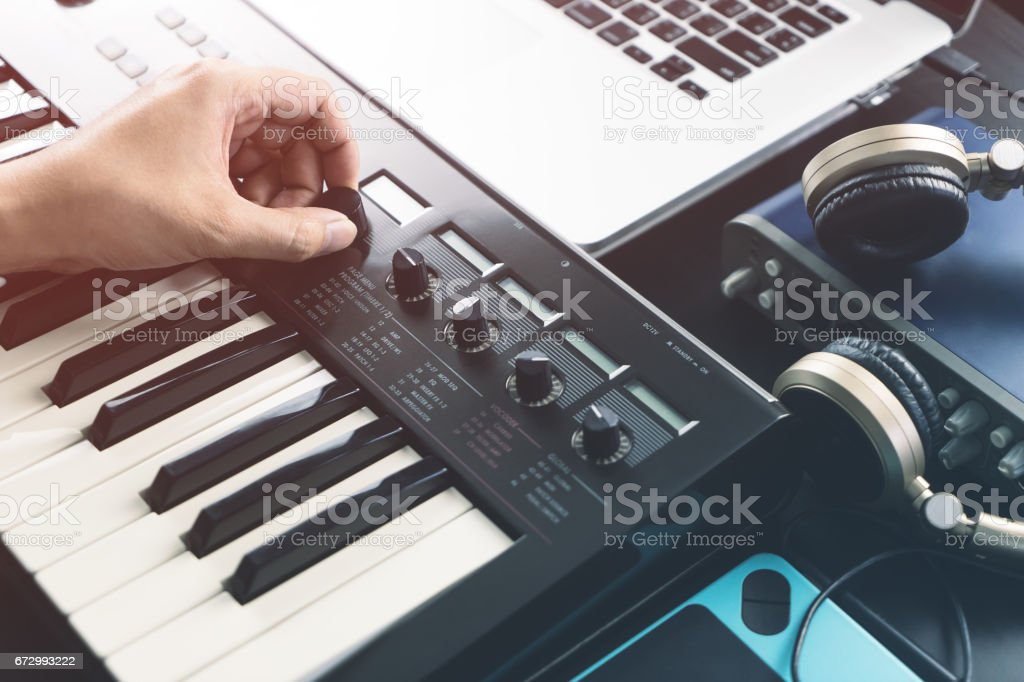 Musician is adjusting sound on synthesizer keyboard stock photo