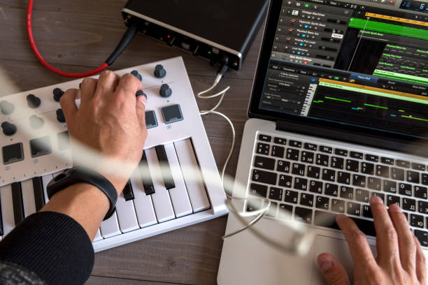Musician is recording tunes on his computer music. first-person view stock photo