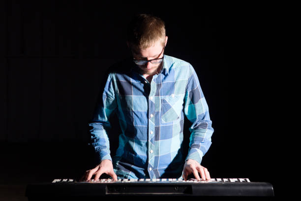 Musician man play keyboard on dark background stock photo
