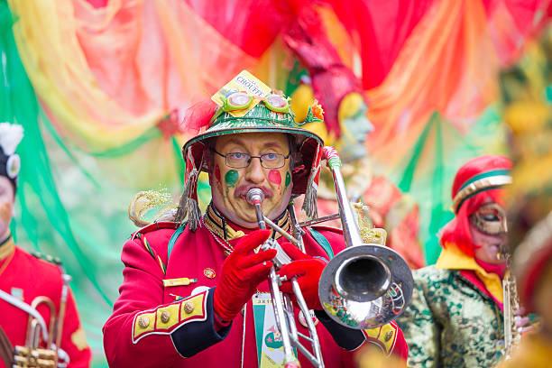 musician marching in red costume at carnival parade of maastricht - maastricht stockfoto's en -beelden