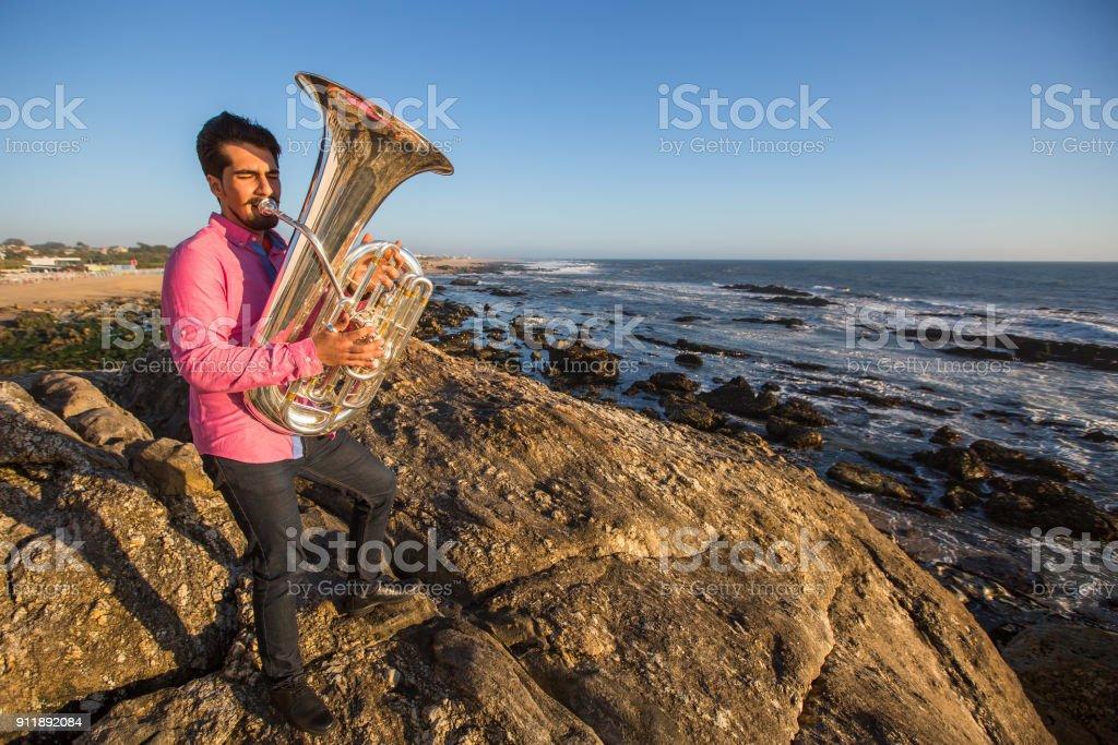 Musician play to Tuba on romantic ocean shore. stock photo