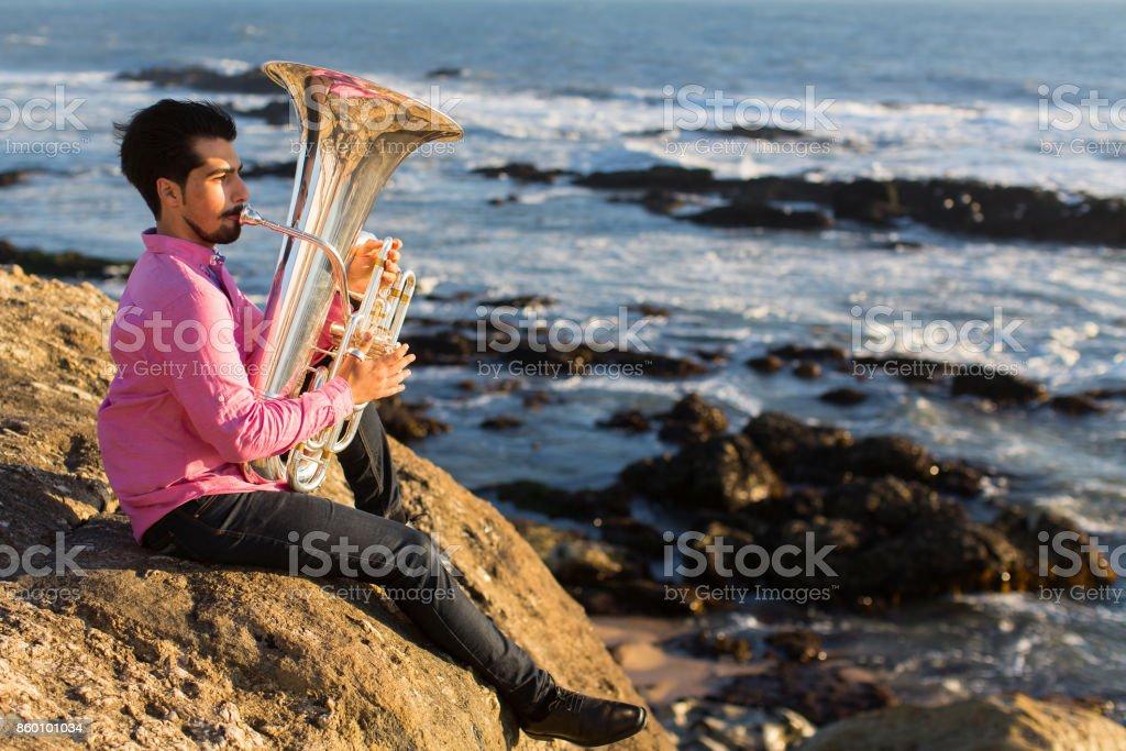 Musician play Tuba on sea beach. stock photo