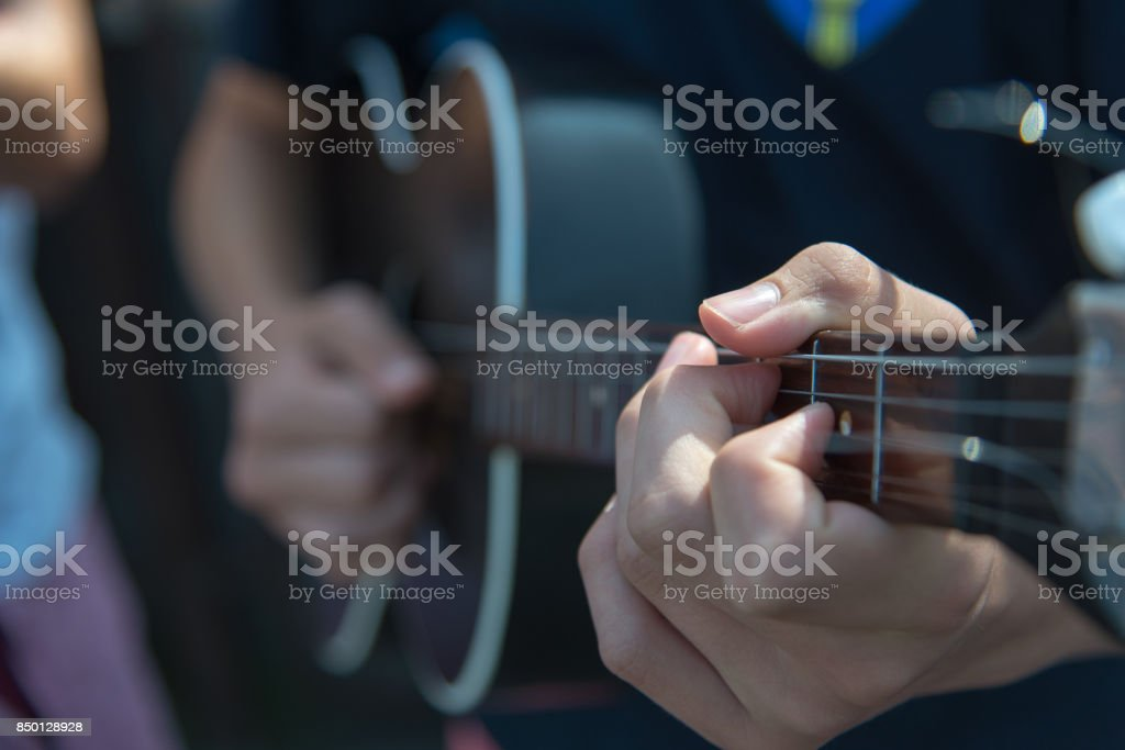 Musician playes a string musical instrument, called tambura. Close up. stock photo