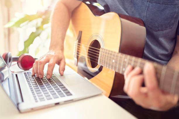 Musician playing acoustic guitar and recording music on computer stock photo