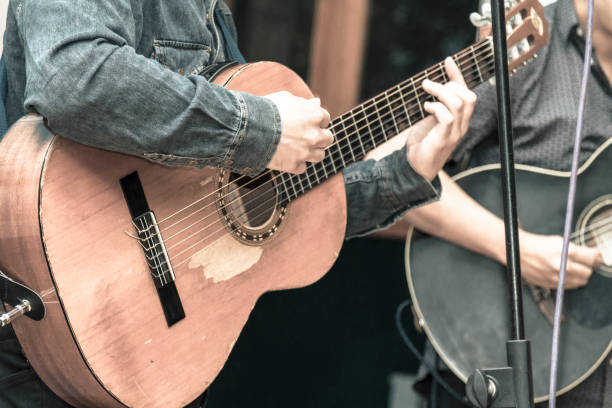 Musician playing acoustic guitar in a concert show Two males musicians playing acoustics guitars in a concert show. Close shooting of hands playing a wood made guitar, the artists are dressing by jean jacket and blue t-shirt. country and western music stock pictures, royalty-free photos & images