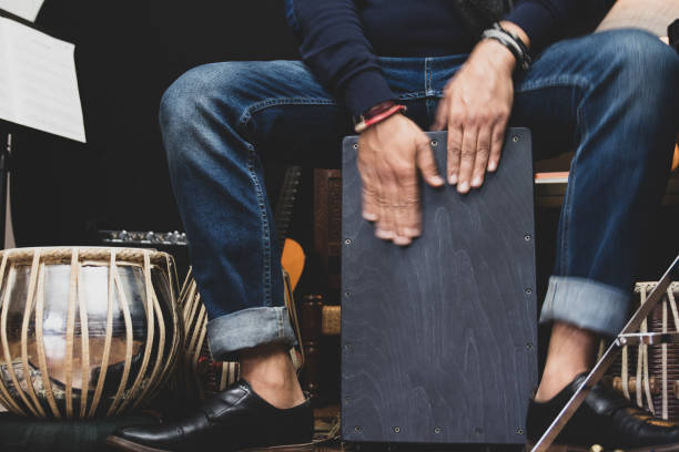 A musician playing Cajon drums. A stylish musician in denim and double monk shoes plays the Cajon, a Peruvian drum used commonly with Spain's Flamenco dance. percussion instrument stock pictures, royalty-free photos & images