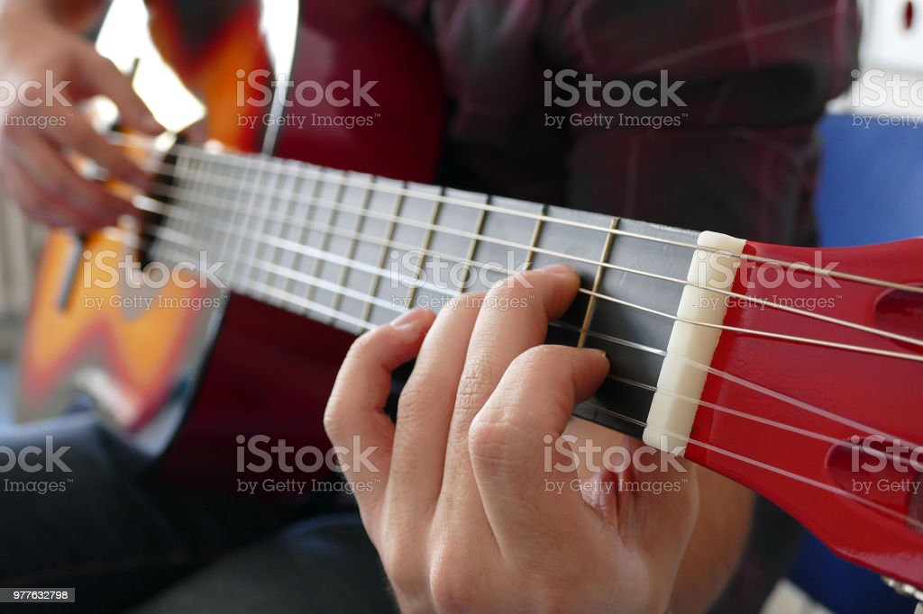 Musician playing electric guitar melody. Details of the strings and right hand near the pickups. stock photo