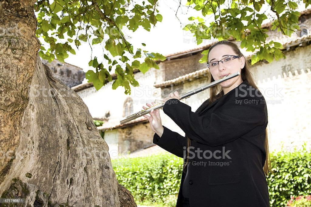 Musician playing flute in nature royalty-free stock photo