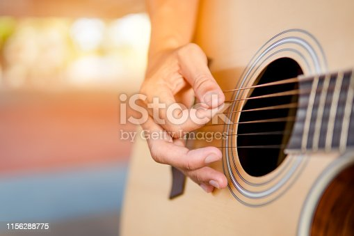 Musician playing guitar classic and singing song, close up hand
