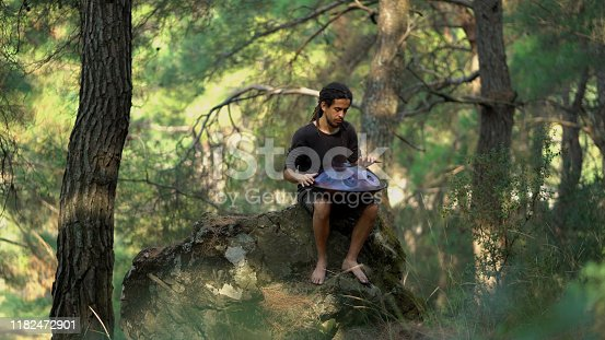 Musician playing handpan in forest.