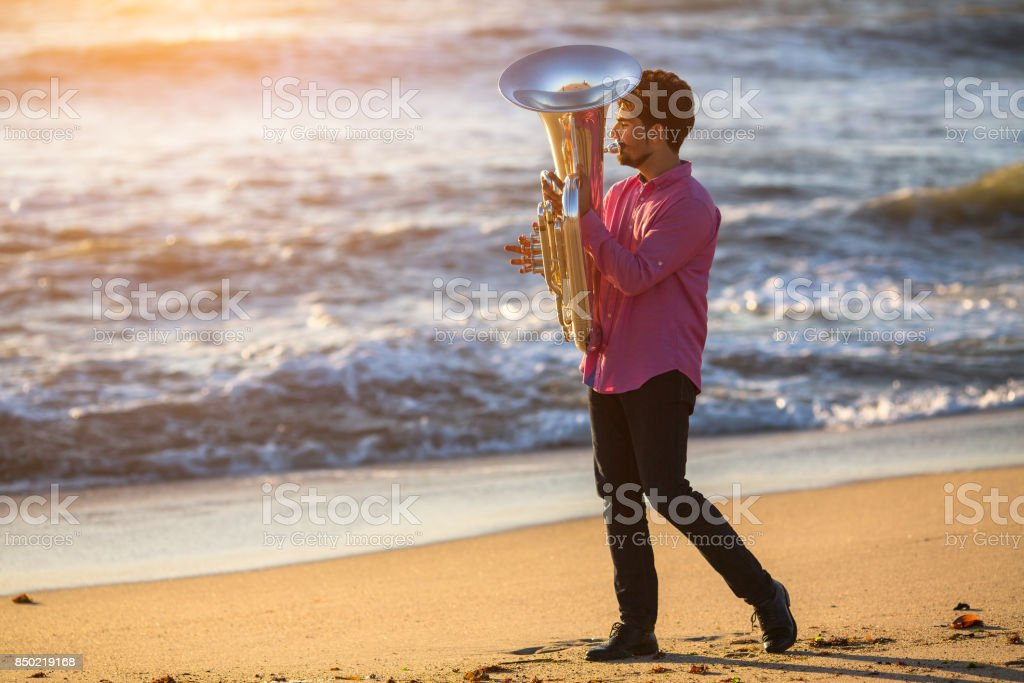 Musician playing musical instrument Tuba on the sea beach. stock photo