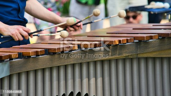 Musician playing on a marimba, an instrument from the group of xylophones