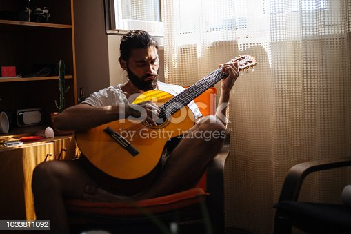 Musician playing on acoustic guitar in the living room. He enjoys and sings, and it is in the sunset.