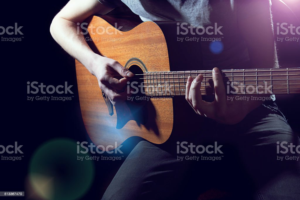 Musician playing on acoustic guitar stock photo