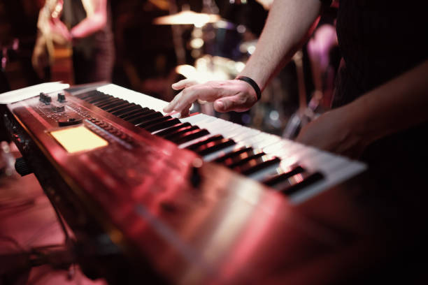 Musician playing on the keyboard synthesizer piano keys. Musician plays a musical instrument on the concert stage Musician playing on the keyboard synthesizer piano keys synthesizer stock pictures, royalty-free photos & images