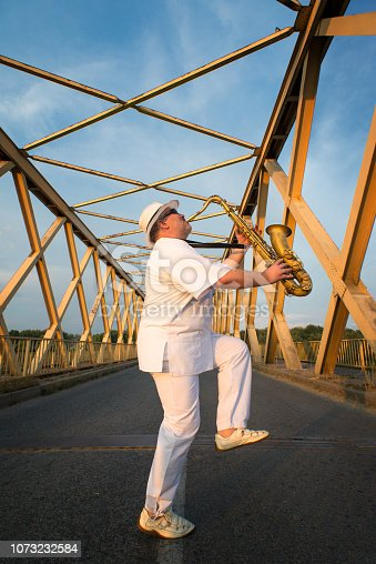 Musician playing saxophone in the middle of the bridge on a sunny summe day.