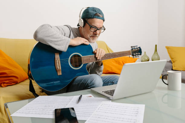 Musician playing the guitar and composing music with his colleagues by video conference through his laptop stock photo