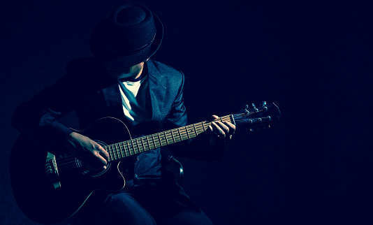 Musician playing the guitar on black background,music concept
