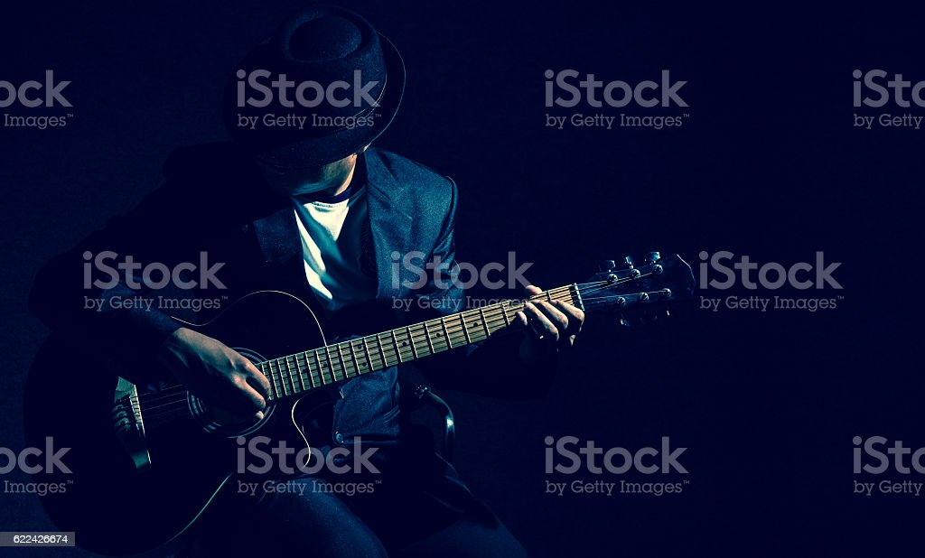 Musician playing the guitar on black background,music concept - Photo