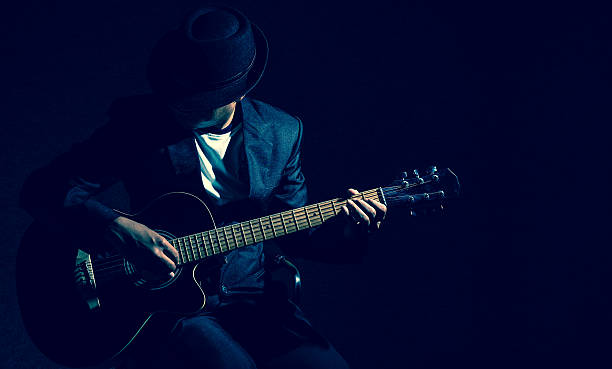 Musician playing the guitar on black background,music concept - foto de acervo