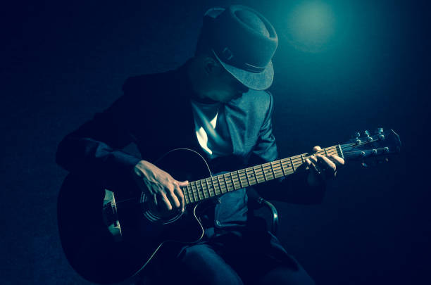 Musician playing the guitar on black background,music concept Musician playing the guitar on black background,music concept guitarist stock pictures, royalty-free photos & images