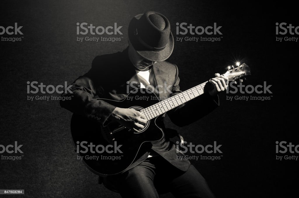 Musician playing the guitar on black background,music concept stock photo