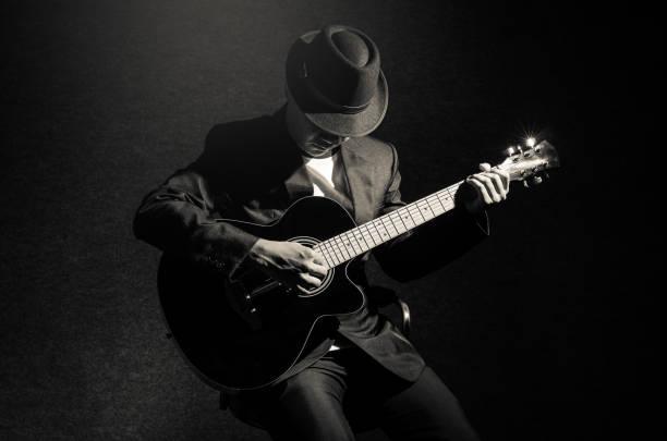 musiker, gitarre zu spielen, auf schwarzem hintergrund, musikkonzept - blues stock-fotos und bilder