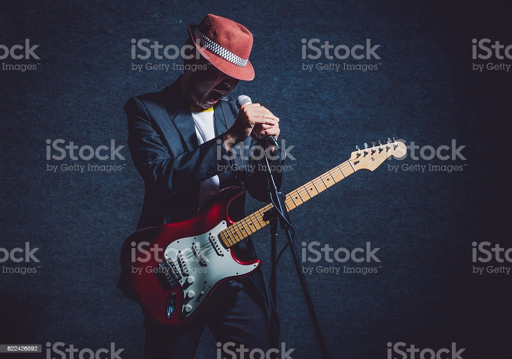 Musician playing the guitar with hand holding the microphone stock photo
