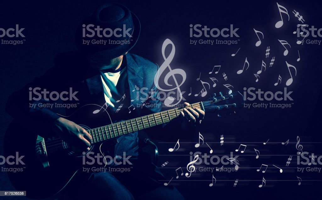 Musician playing the guitar with music notes on black background,music concept stock photo
