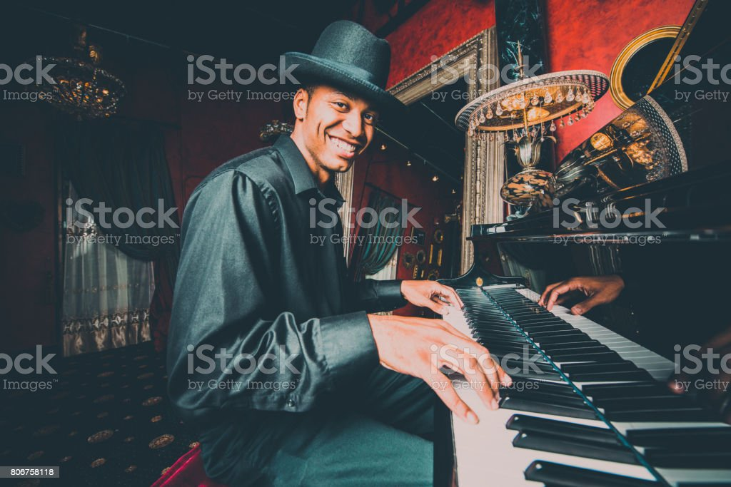 Musician playing the piano in nightclub bar stock photo