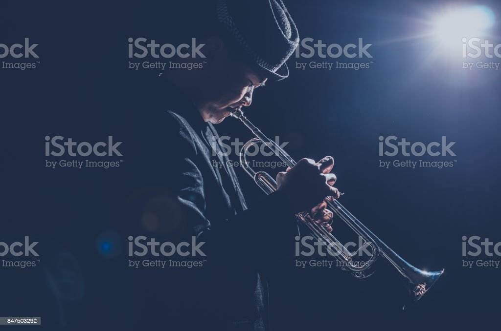 Musician playing the Trumpet with spot light and len flare on the stage stock photo