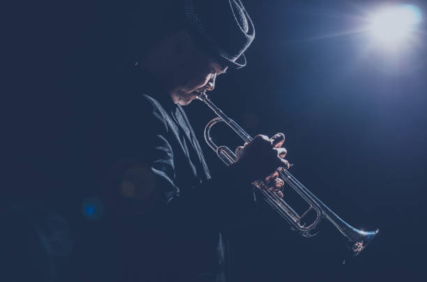 musician playing the trumpet with spot light and len flare on the stage - musician stock photos and pictures
