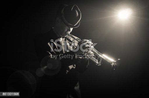 istock Musician playing the Trumpet with spot light on the stage 851331568