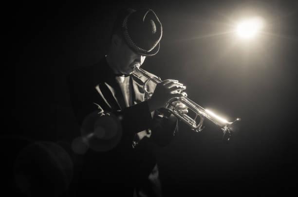 sahne alanı'nda trompet spot ışığı ile oynarken müzisyen - caz stok fotoğraflar ve resimler