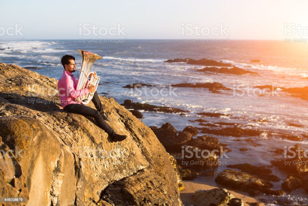 Musician playing the Tuba on the sea shore. stock photo