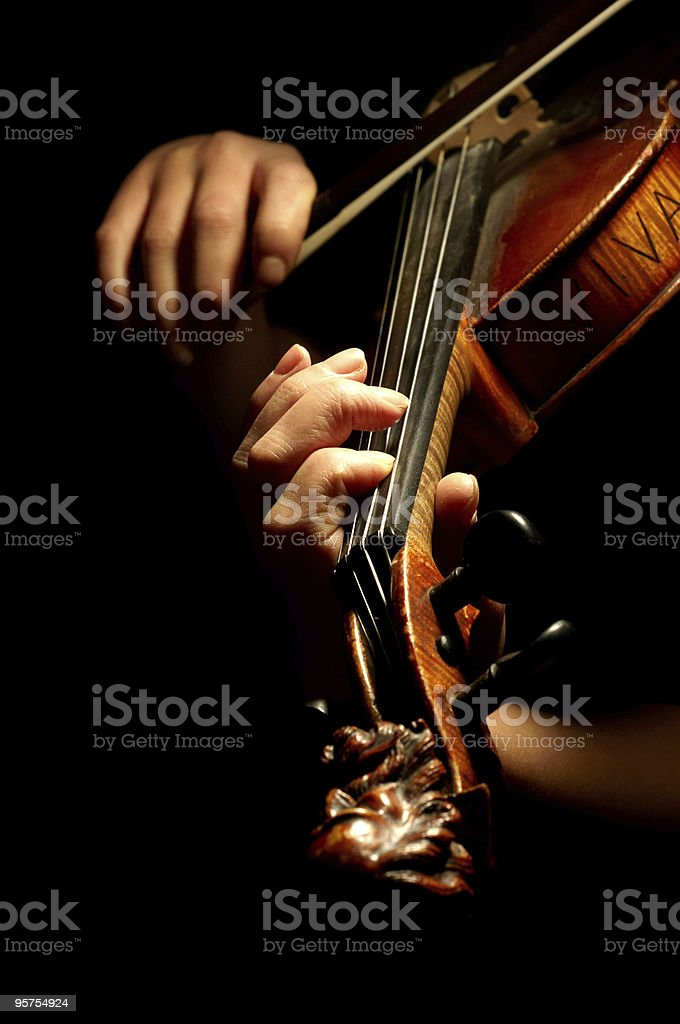 A musician playing the violin in the dark stock photo